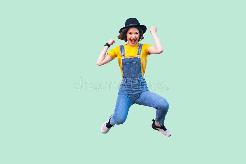 Portrait of screaming happy suprised young girl in blue denim overalls, yellow shirt and black hat jumping, looking and royalty free stock images