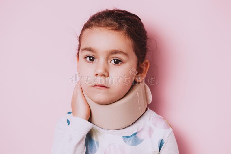 Portrait of Little girl wearing neck brace on pink background. Portrait of screaming Little girl wearing neck brace on pink background. childhood injuries royalty free stock images