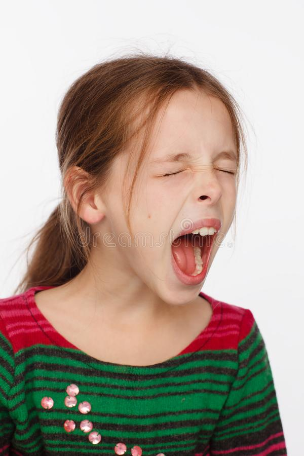 Portrait of a screaming 8-year-old girl in a sweater in crimson and green stripes. Studio photo session. White background stock photo