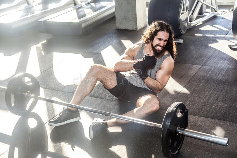Portrait of screaming young adult man athlete with long curly hair working out in gym, sitting on floor and have strong hurt. Problem with wrist, spasm painful stock photo