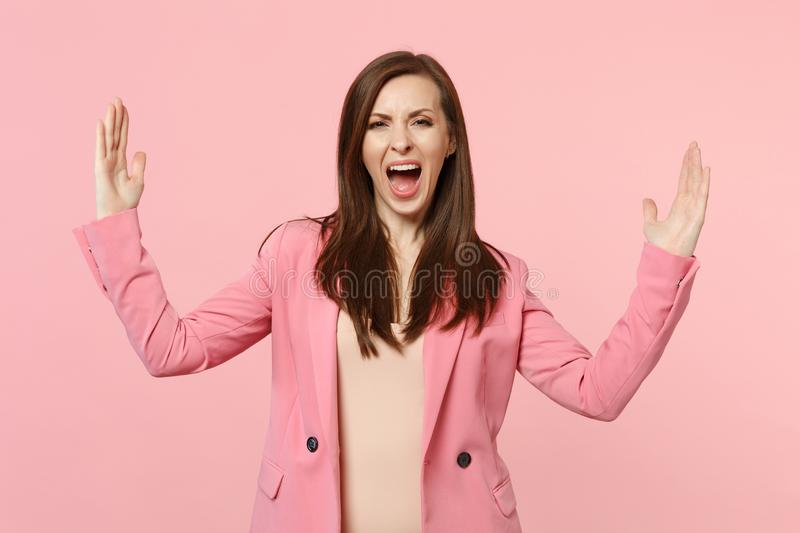 Portrait of screaming young woman in jacket gesturing demonstrating size with horizontal workspace isolated on pastel. Pink background. People sincere emotions stock photos