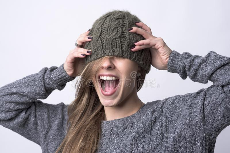 Portrait of screaming young woman with knitted cap covering her eyes royalty free stock images