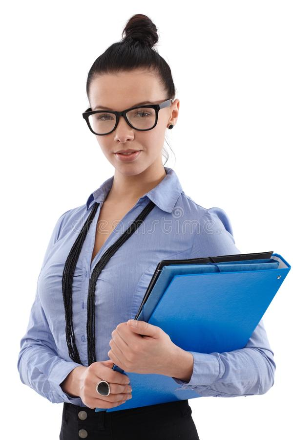 Portrait of secretary with folders. Portrait of young secretary with knot and glasses holding folders royalty free stock photo