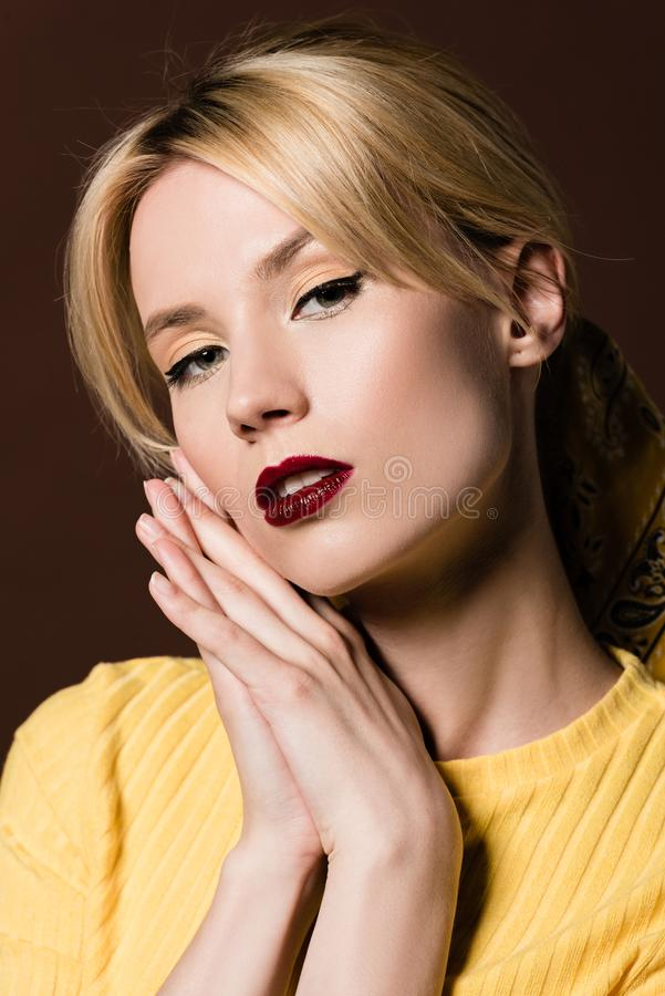Portrait of seductive blonde girl looking at camera. Isolated on brown royalty free stock image