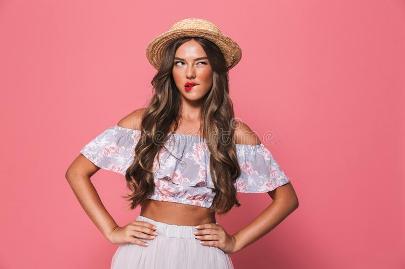 Portrait of seductive european woman 20s wearing straw hat biting lips and holding arms on waist, isolated over pink background i stock image