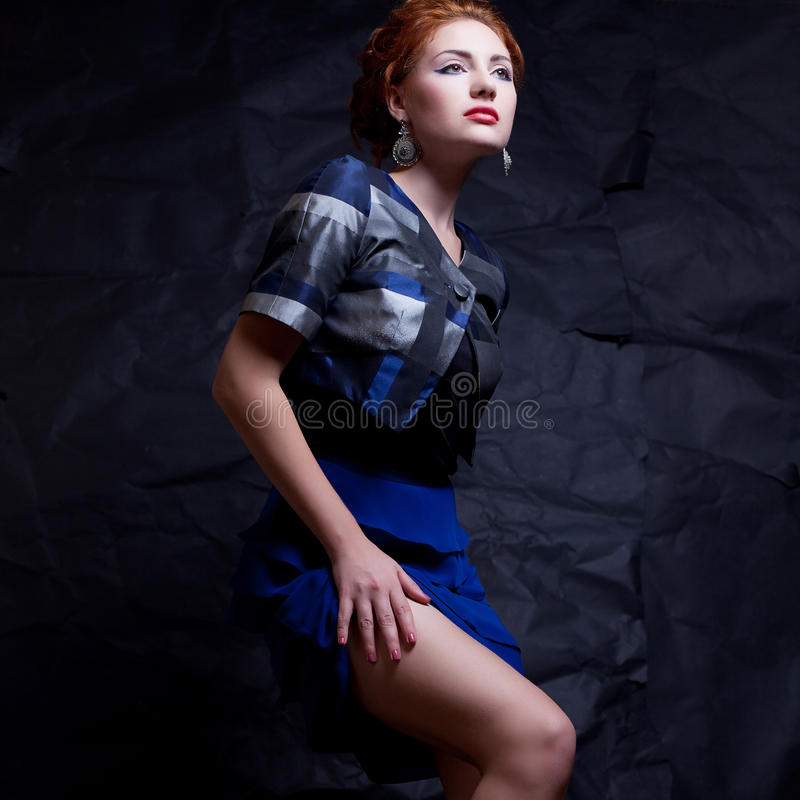 Portrait of seductive ginger model in vintage costume a-la 80s. Portrait of a seductive ginger model in vintage costume a-la 80s posing over wrinkled black paper royalty free stock photography
