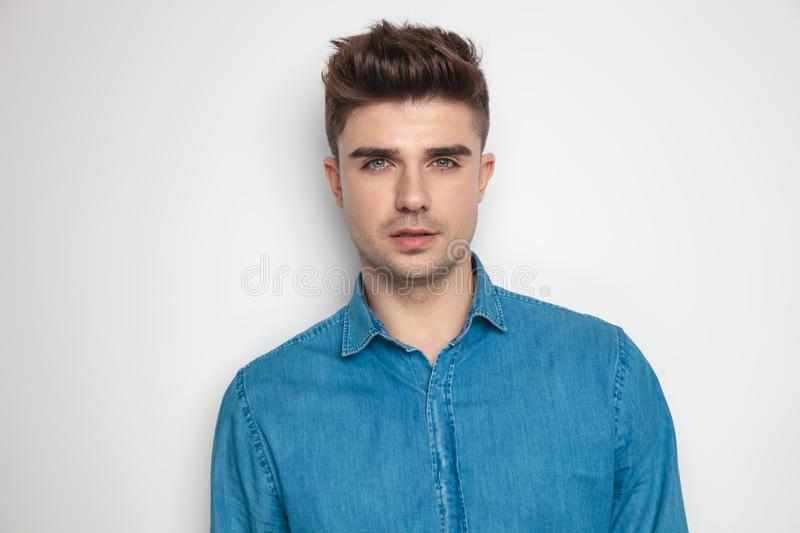 Portrait of seductive young student posing with parted lips. While standing on light grey background stock photos