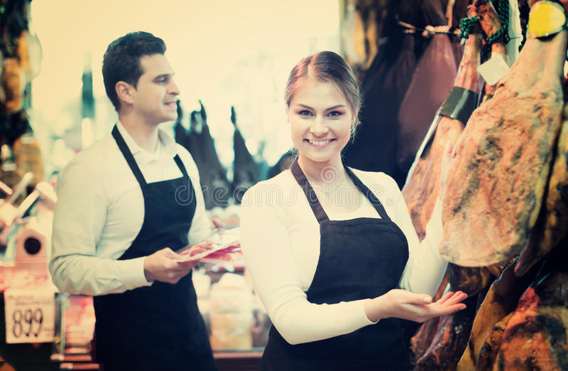 Portrait of sellers offering tasty jamon royalty free stock images