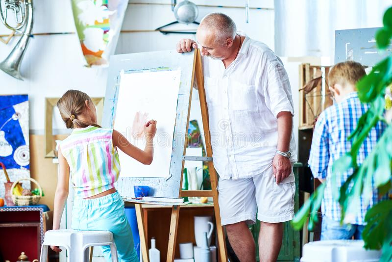 Children Painting in Art Class. Portrait of senior art teacher leaning over easel to watch little student painting pictures on easel in art school, copy space royalty free stock photography