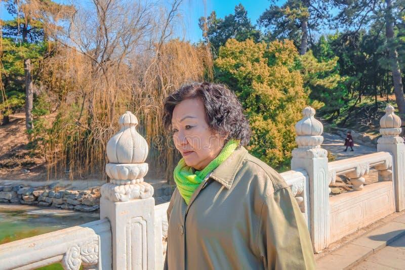 Portrait senior asian women Stand on the bridge in Summer palace park in beijing. Portrait senior asian woman Stand on the bridge in Summer palace park in stock image