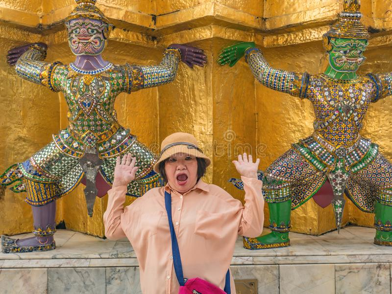 Portrait of Senior asian women make a surprise with Giant lift the pagoda in Wat Phrakaew temple Bangkok Thailand. Portrait of Senior asian woman make a surprise stock photo