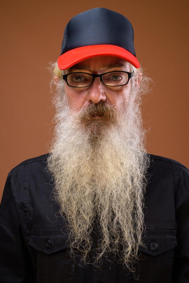 Portrait of senior bearded man against brown background royalty free stock photography