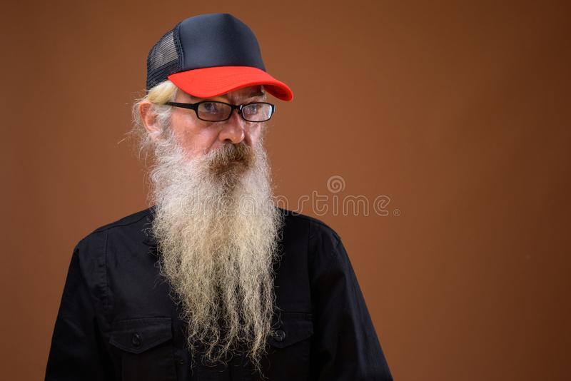 Portrait of senior bearded man against brown background royalty free stock images