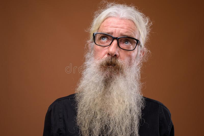 Portrait of senior bearded man thinking and looking up royalty free stock photography