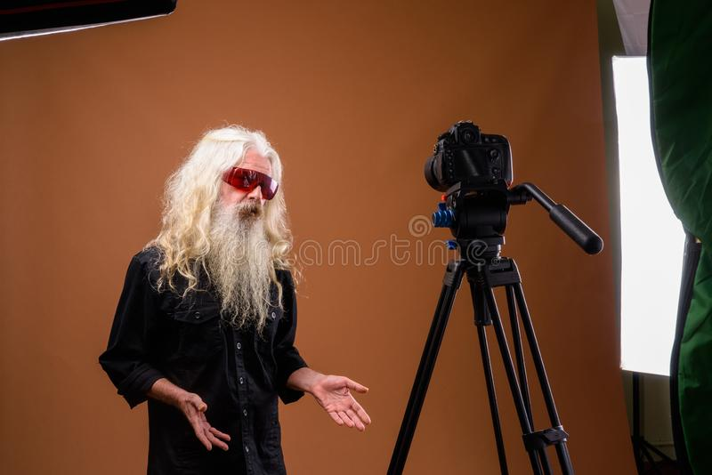 Portrait of senior bearded man vlogging in studio royalty free stock photography