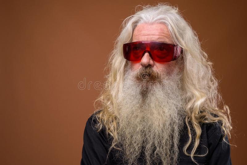 Portrait of senior bearded man wearing red glasses and thinking stock image