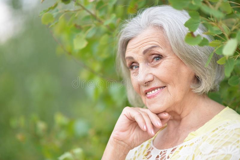 Portrait of senior beautiful woman in spring park. Senior beautiful woman posing in spring park royalty free stock image