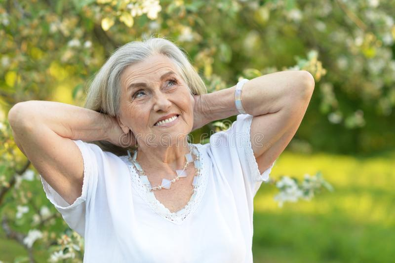 Portrait of senior beautiful woman in spring park. Senior smilling beautiful woman posing in spring park royalty free stock photo