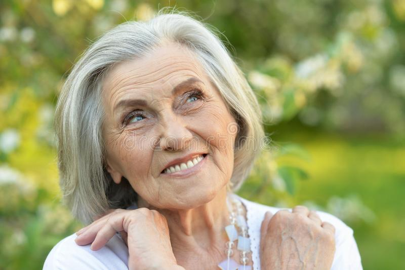 Portrait of senior beautiful woman in spring park. Senior smilling beautiful woman posing in spring park stock photography