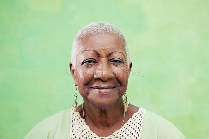Portrait of senior black woman smiling at camera on green background stock photography
