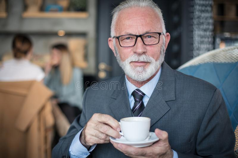 Portrait of senior businessman with a cup of coffee. stock image