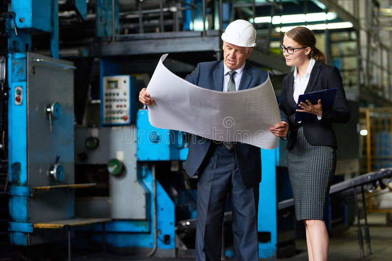 Senior Inspector Looking at Factory Plans royalty free stock image