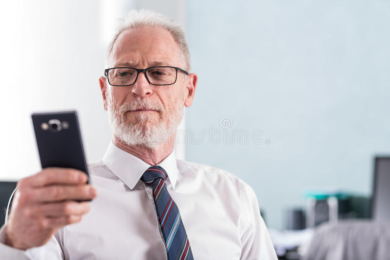 Portrait of senior businessman looking at his mobile phone stock photography