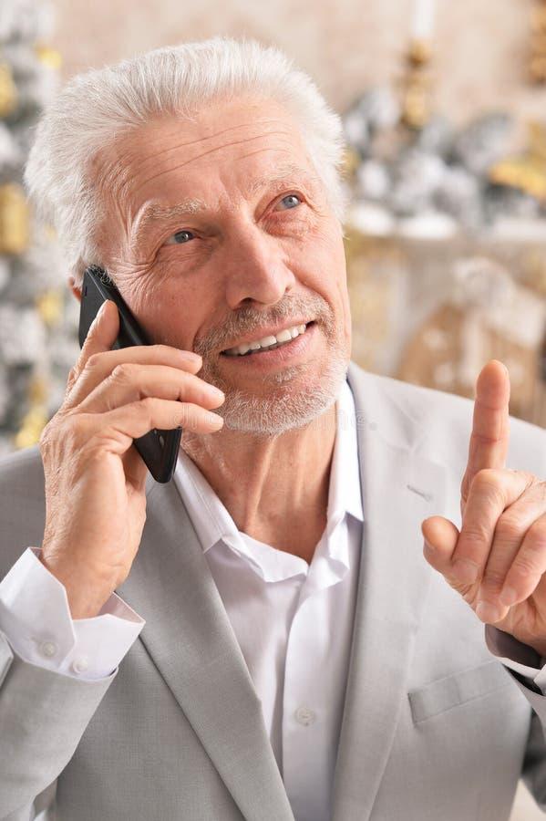 Portrait of senior businessman talking on phone stock photos