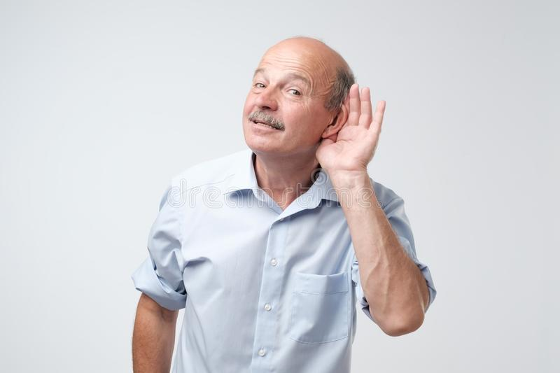 Portrait of senior casual man which overhears conversation over white background. Speak loudly please concept. stock photography