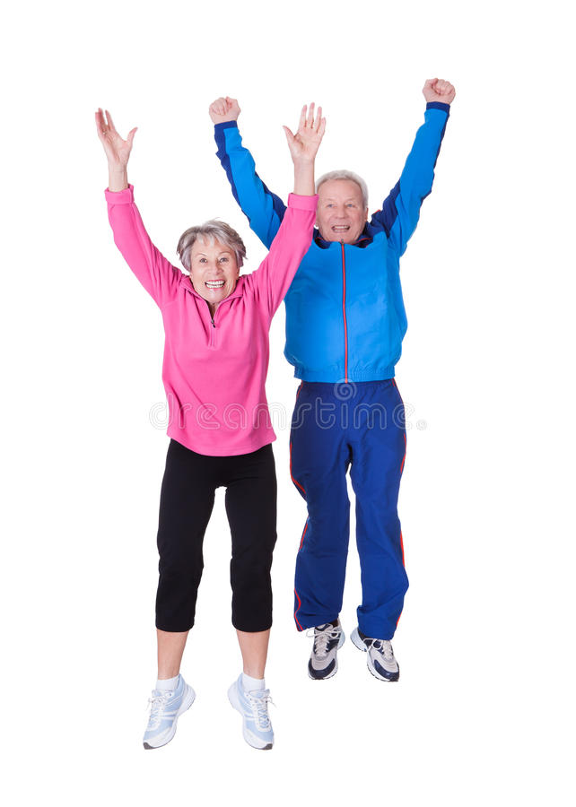 Portrait of senior couple jumping in joy royalty free stock images