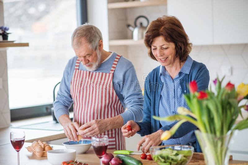 A portrait of senior couple in love indoors at home, cooking. stock photo