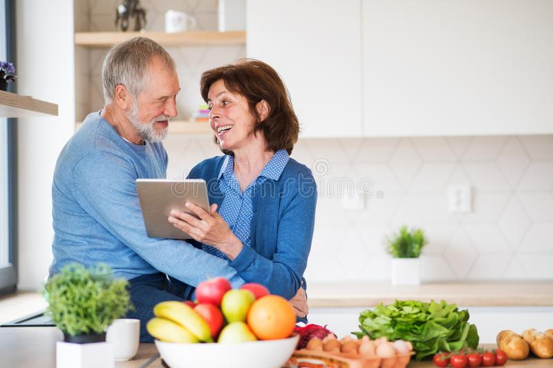 A portrait of senior couple in love indoors at home, using tablet. A portrait of happy senior couple in love indoors at home, looking for recipe using tablet stock photos