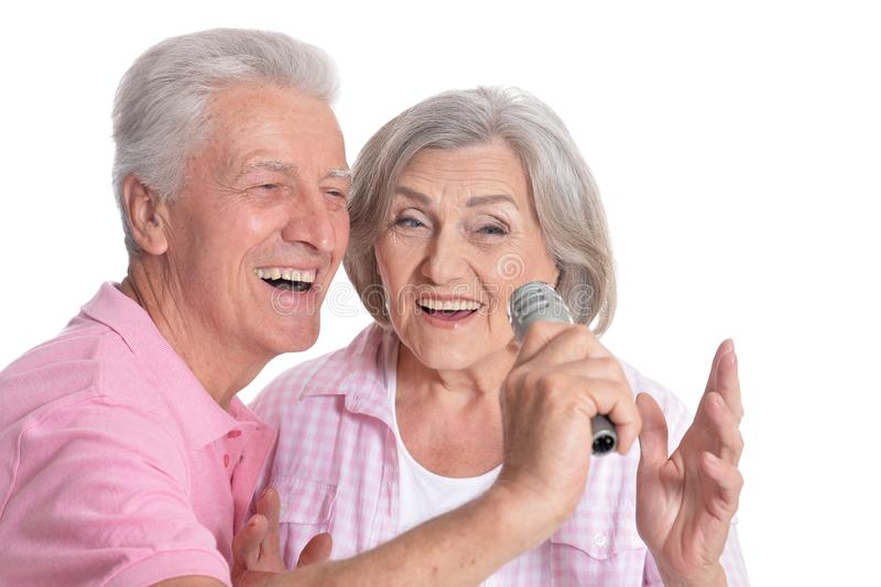 Portrait of Senior couple singing with microphone. On white background royalty free stock photography