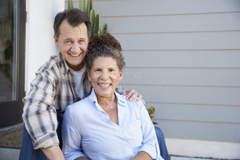 Portrait Of Senior Couple Sitting Outside Grey Clapboard House royalty free stock photography