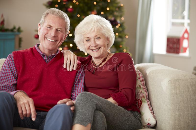 Portrait Of Senior Couple Sitting On Sofa In Lounge At Home On Christmas Day stock image