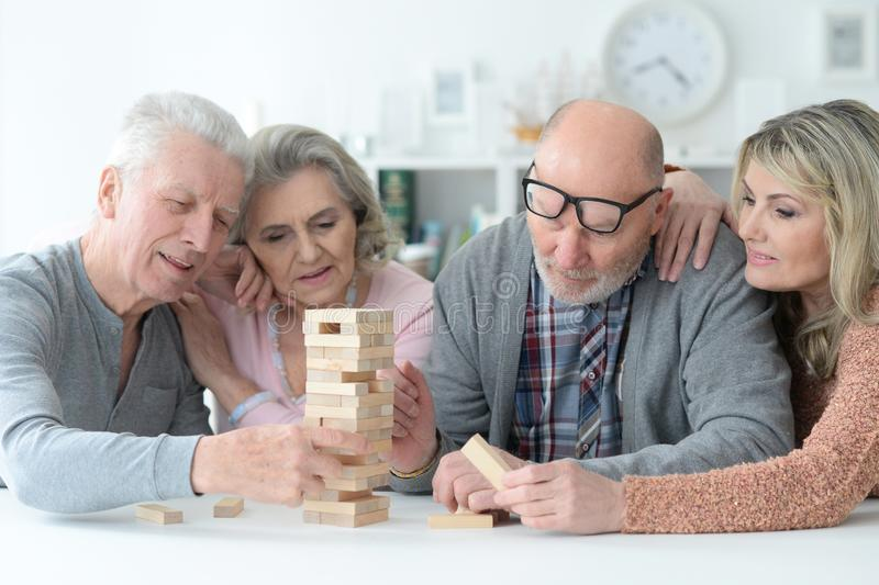 Portrait of senior couples playing with wooden blocks. Two senior couples sitting at table and playing with wooden blocks stock photography