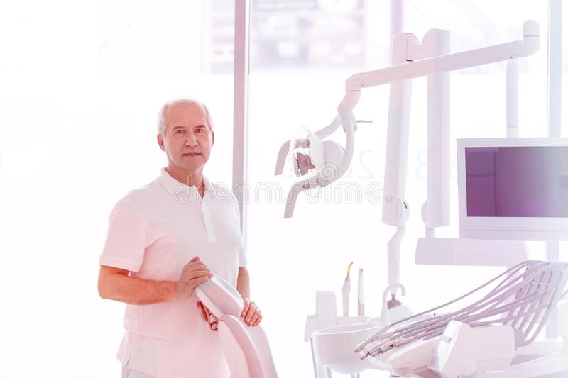 Portrait of senior dentist standing by chair at dental clinic stock images