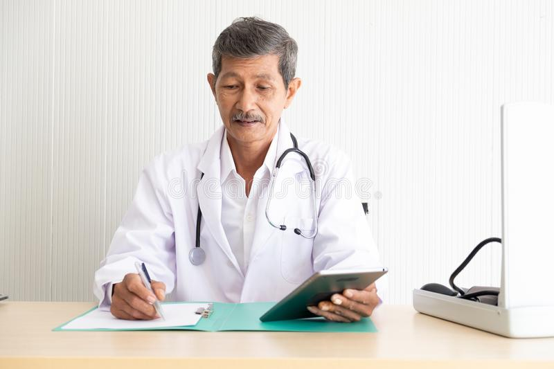 Portrait of a senior doctor check medical information royalty free stock photography
