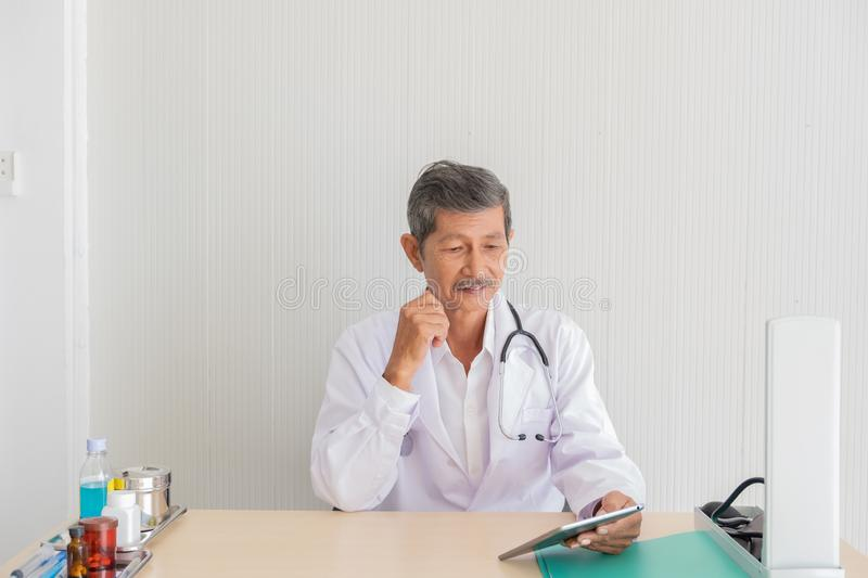 Portrait of a senior doctor check medical information on the tablet royalty free stock photography