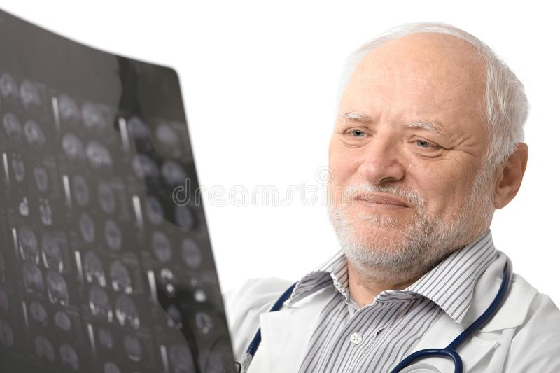 Portrait of senior doctor looking at X-ray image stock image
