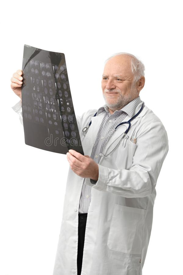 Portrait of senior doctor looking at X-ray image. Portrait of happy senior doctor looking at X-ray image, smiling. Isolated on white background royalty free stock images