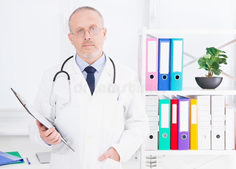 Portrait of senior doctor in medical office.Man in white uniform. Medical insurance. Copy space. Quality medicine concept. Copy sp. Ace royalty free stock image