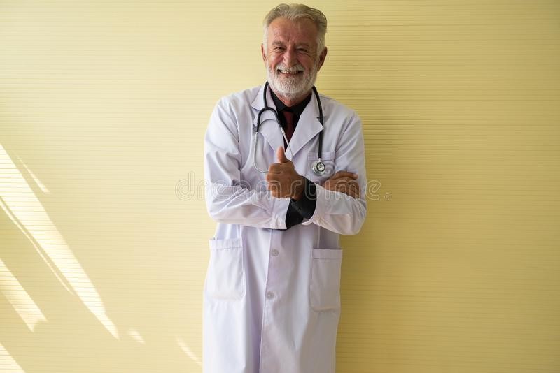 Portrait of senior doctor standing and showing thumb up at hospital,Happy and smiling positive thinking attitude stock photography