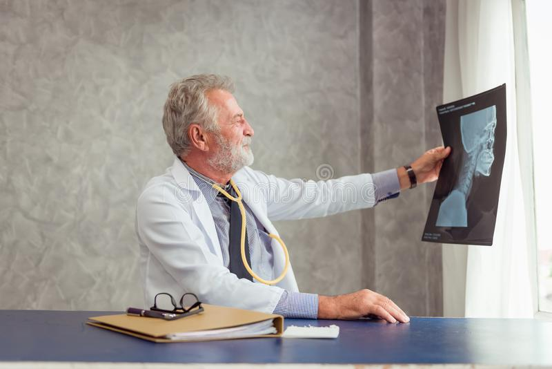 Portrait of senior doctor is working and examining X-Ray film for his patient in examination room, Healthcare and occupational co royalty free stock images