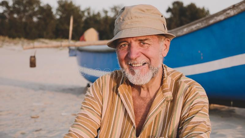 Portrait of senior fisherman in hat near his fishing boat - Sicily stock image