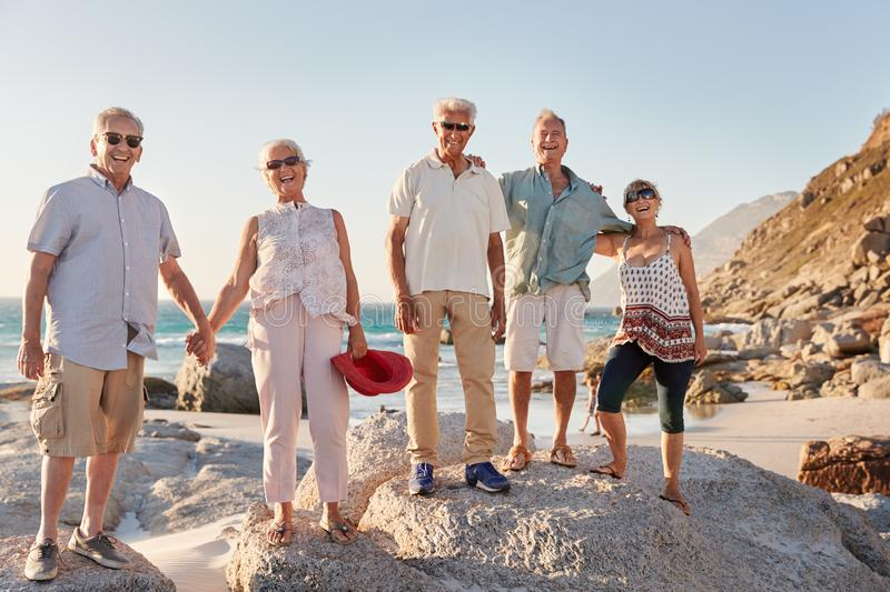 Portrait Of Senior Friends Standing On Rocks By Sea On Summer Group Vacation stock photos