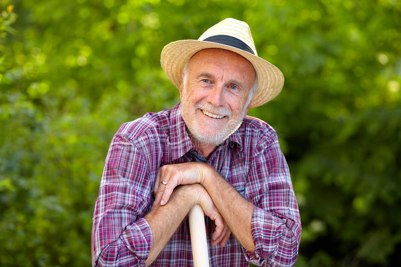 Portrait of senior gardener with straw hat stock photography