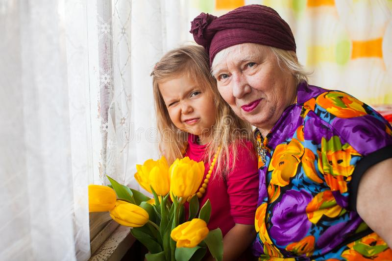 Portrait of senior grandmother with grandaugther with yellow tulips royalty free stock photo