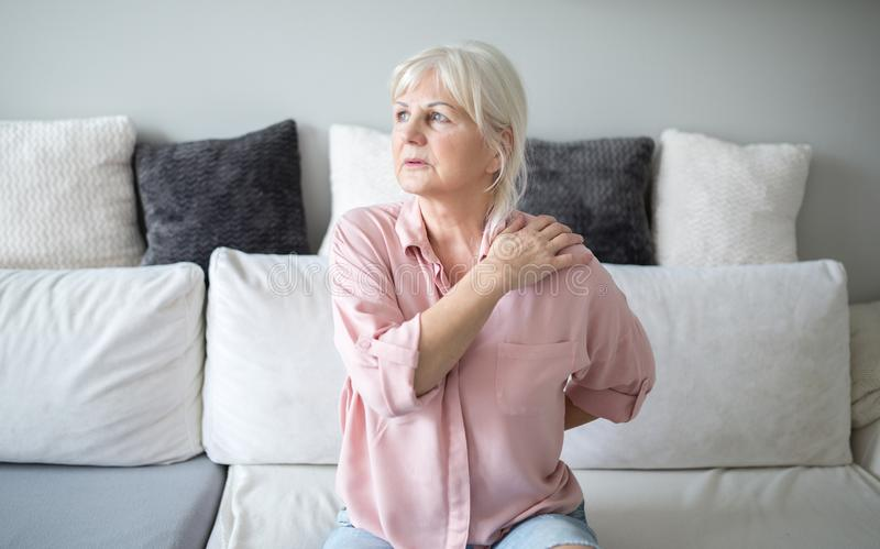 Senior lady with back pain sitting on couch stock photography