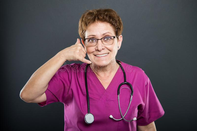Portrait of senior lady doctor showing calling gesture. Portrait of senior lady doctor showing calling or contact gesture on black background stock image